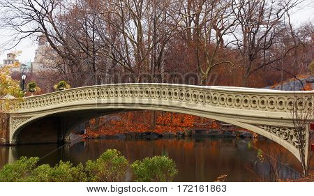 colorful autumn panorama of the bow bridge in Central park red green and yellow colors dominate the picture.
