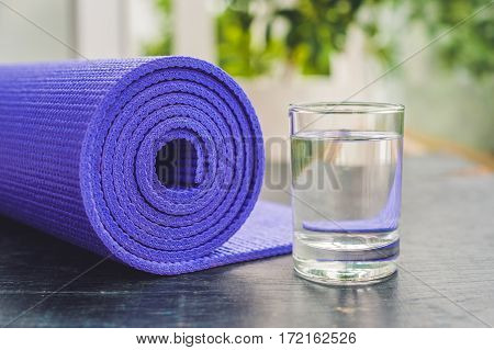 Yoga Mat, Water, Orange And Mango On A Wooden Background. Equipment For Yoga. Concept Healthy Lifest
