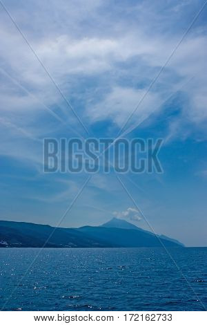 Scenic view of Mount Athos from see with two contrails forming the cross shape in the sky, Greece