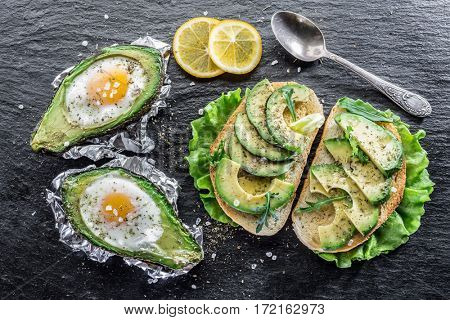 Avocado sandwich and Chicken egg baked in avocado. Delicious meals.