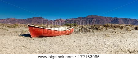 Red boat in desert. landscape photo: lost red boat in the desert of cabo de gata (Andalusia) with the mountains in the background.