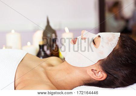 Prettyl Woman With Facial Mask At Beauty Salon. Spa Treatment