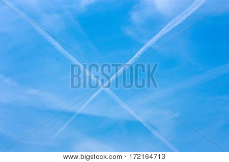 Airplanes' condensation trails form cross on the heavenly blue sky