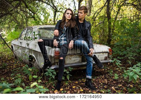 Young man and woman sitting on the hood of an old abandoned car in the middle of thickets of bushes and trees. Summertime