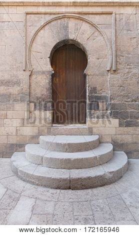Wooden aged vaulted door three steps and stone wall Medieval Cairo Egypt
