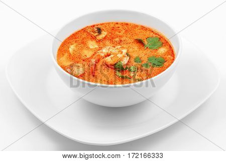Tom Yam soup, shrimp and mushrooms in a white plate on a white background
