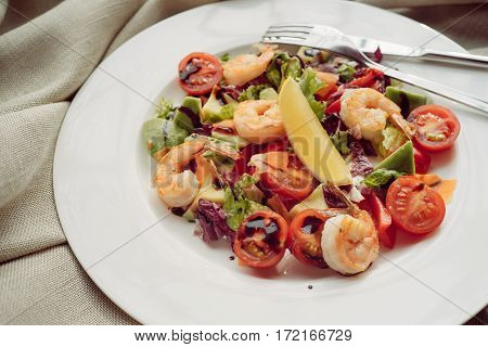 Green salad with shrimp and avocado on white plate