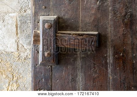 Front view closeup of a wooden aged latch over a wooden opened door