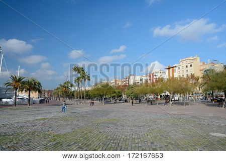 Barcelona Spain - December 3 2016: Pla de Miquel Tarradell square trees and buildings in Barcelona Spain. Unidentified people visible.