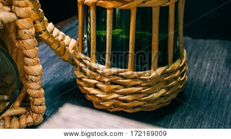 Wicker wine bottle next to wine basket on black table. Partly viewed