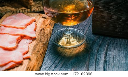 Sliced ham on rustic wood board. Snifter of brandy on black table