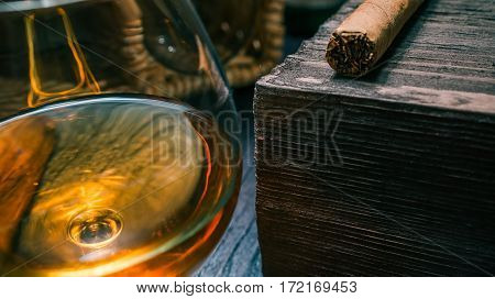 Cigar on dark wood stand. Snifter of brandy next to it. Closeup view