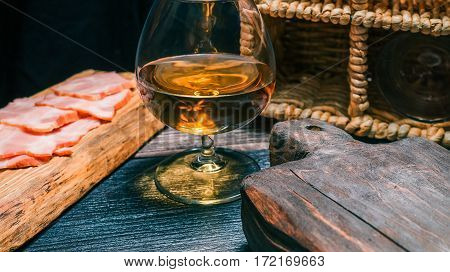 Sliced ham on rustic wood board. Snifter of brandy, wine basket and other serving board on black table.