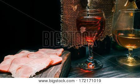 Sliced ham on rustic wood board. Red wine and brandy on black table