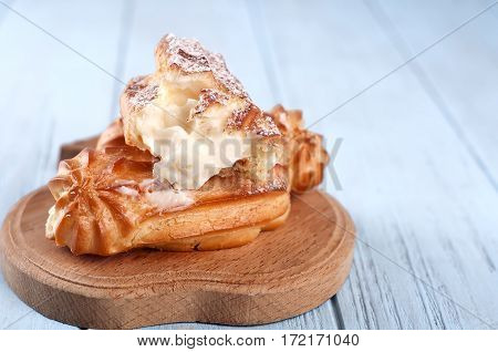eclairs on a wooden Boards on a blue wooden background