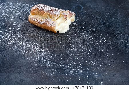 eclair with powdered sugar and cocoa on the concrete a dark background