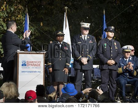 NEW YORK - 11 NOV 2016: 2016 Grand Marshals Stephanie Dawson, Joseph Duggan Jr., and Nelson Vergara, and other VIPs on stage at the Veterans Day ceremony in Madison Square Park.