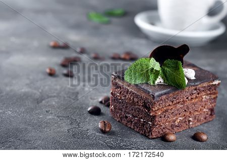 chocolate cake with mint, cup of coffee on a dark concrete background.