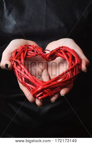 Woven wicker red heart in woman hands on black background. Closeup of a heart in her hand. Happy women's day, the concept of love.