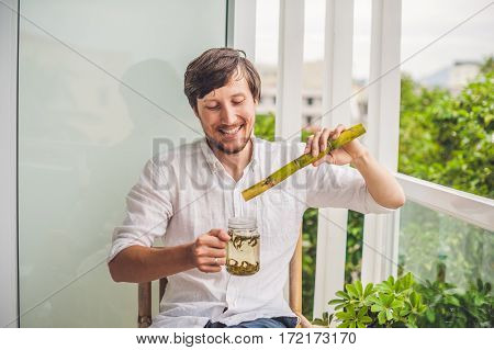 Cane Sugar Concept. The Man Jokingly Eating Sugar Cane And Drinks Tea