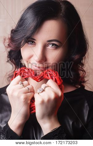 Sexy brunette model girl with red heart in hands love symbol, happy woman, Perfect makeup, women's day.