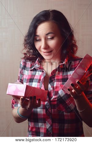 Sexy model girl in plaid shirt opens a Valentine gift. Happy woman, women's day. The brunette lady surprised by gift in the box.
