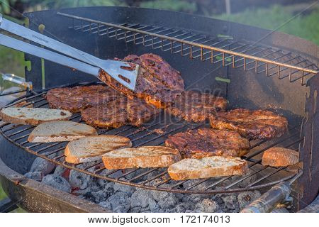 Steaks and bread on the grill in the garden