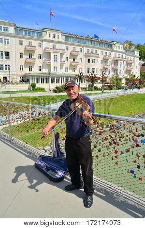 Salzburg austria - april 25: a street performer with his violin in salzburg austria. shot taken on april 25th 2015