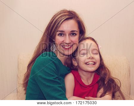 Motherhood is happiness. Beautiful young woman hugging little girl smiling and looking at her with love. Mother and daughter having fun together