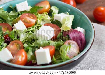 Salast with cherry tomatoes, Radicchio lettuce, frize, arugula and feta on wooden table