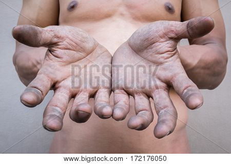 Dirty hands of male workers. Selective focus. Abstract background.