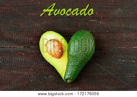 Fresh avocado in the shape of a heart isolated on wood table background. Love symbol made of fruit. Exotic fruit.