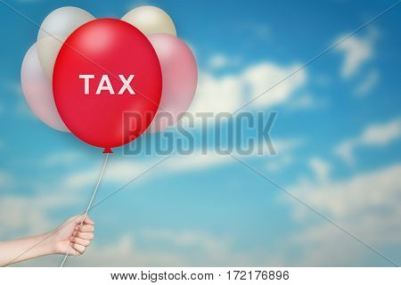 Hand Holding tax Balloon with sky blurred background
