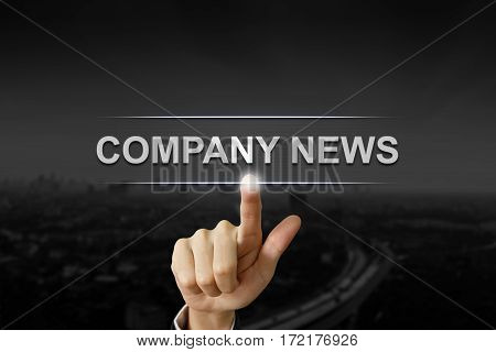 business hand clicking company news button on black blurred background