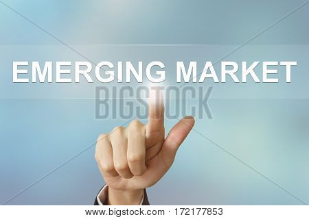 business hand pushing emerging market button on blurred background