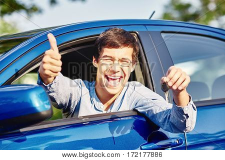 Close up of young happy hispanic man wearing glasses holding out car keys, showing thumb up hand gesture and laughing through car window - driving school and new drivers concept