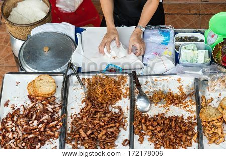 Woman monger wrapping the fried pork with sticky rice in stall.