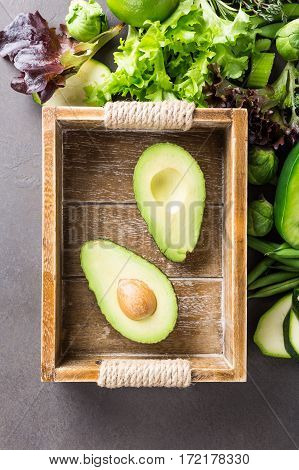 Avocado in wooden tray with assorted green vegetables, salad, bell pepper and Brussels sprouts on light brown stone table top. Healthy food concept with copy space.