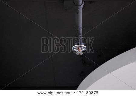 Fire sprinklers put on the black ceiling of modern office.
