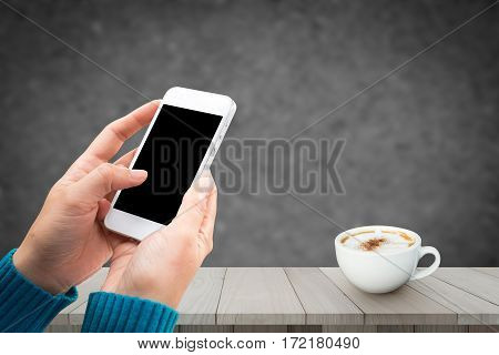 Woman hand holding and using mobile phone, smart phone with isolated screen and redolent cappuccino coffee on wooden floor with blurred image of abstract background.
