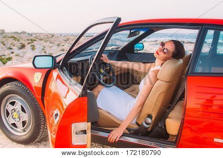 Young Girl In White Dress Sitting On The Front Seat Of The Red Ferrari