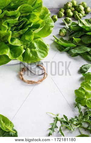 Background with assorted green vegetables, fresh lettuce salad, spinach, rucola, Brussels sprouts and basil on light gray stone table. Healthy food concept with copy space.