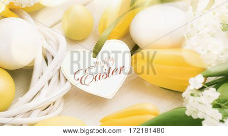 Easter decoration with yellow tulips and greeting label in sunlight