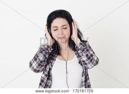 Young woman or girl listening to her favorite song closed eyes and holding big headphones with hands. She enjoys good music and pleasant melody.