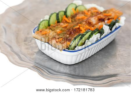 In a ceramic dish on the table fried fish with lettuce and cucumber. Dishes with fish is on a metal tray.