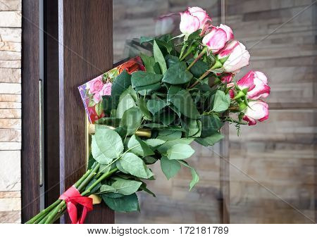 On the front door attached to a beautiful bouquet of roses and a congratulatory letter.