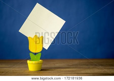 Flowerpot model of note clip on the wood table and blue background.