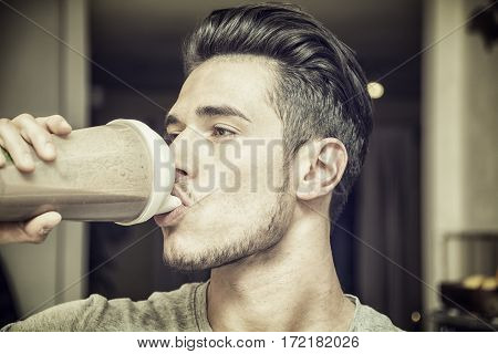 Young man drinking a healthy smoothie drink or a protein shake from blender or shaker