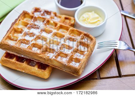 Whole wheat Belgium waffles on plate with butter maple sauce on wooden table close up.