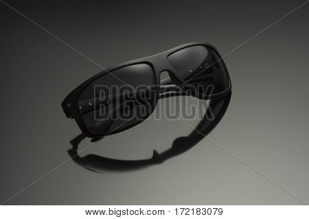 Black sunglasses on a dark background with reflection